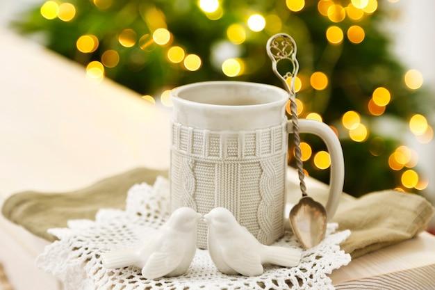 Caneca com bebida quente e enfeites de natal no pinheiro