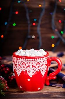 Caneca com cacau e marshmallows com fundo de luzes de guirlanda de natal aconchegante