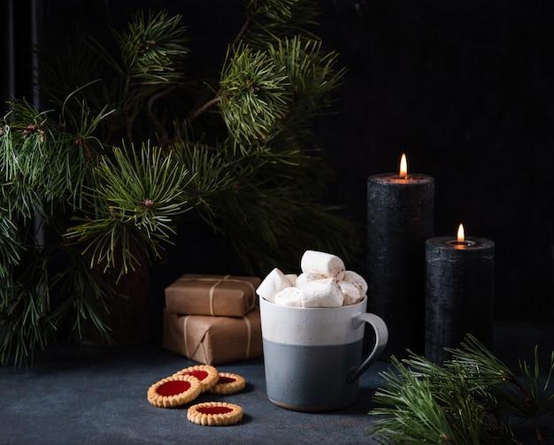 Caneca com cacau, marshmallow e canela em um fundo azul escuro com biscoitos de frutas, velas acesas, presentes e pinheiro. imagem escura e de humor