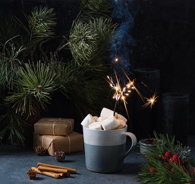 Caneca com cacau, marshmallow e diamante em um fundo azul escuro com canela, presentes e abeto. imagem escura e de humor