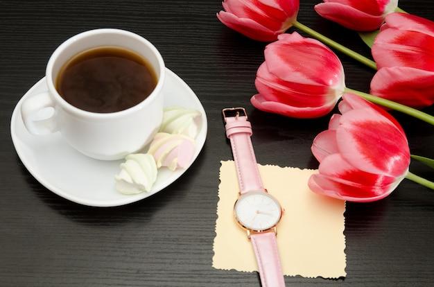 Caneca com café e marshmallow, cartão postal líquido, relógio, tulipas cor de rosa.