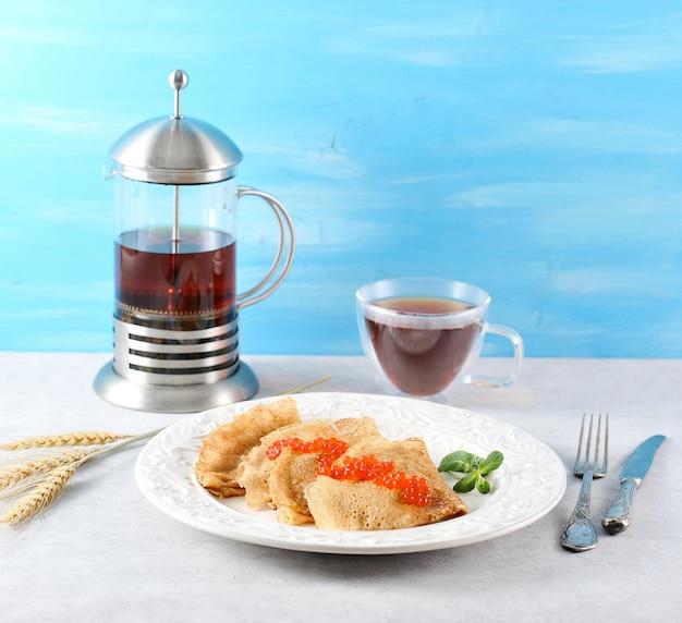 Caneca com chá, chaleira transparente, orelhas e panquecas