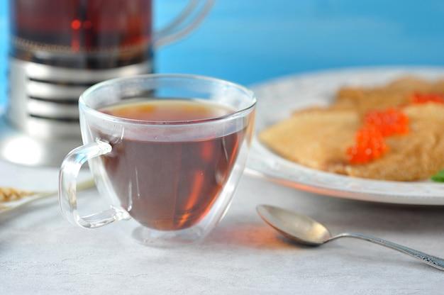 Caneca com chá e panquecas em um prato com caviar