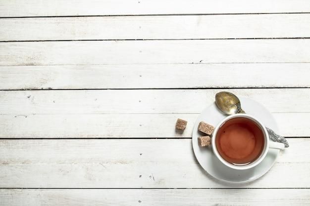 Caneca com chá preto sobre uma mesa de madeira branca