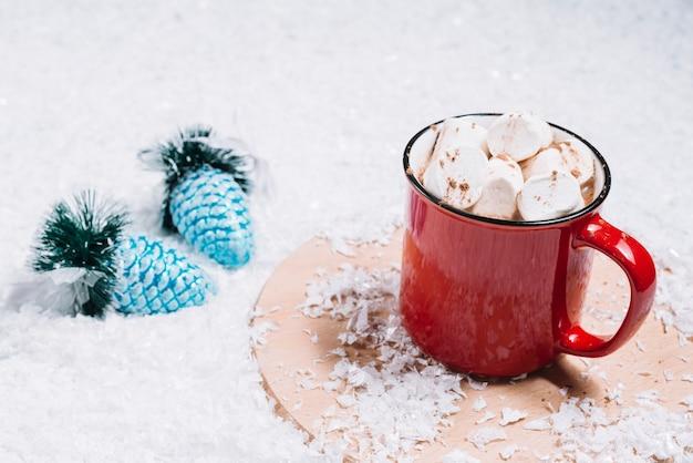 Caneca com marshmallows em stand perto de brinquedos de natal entre a neve