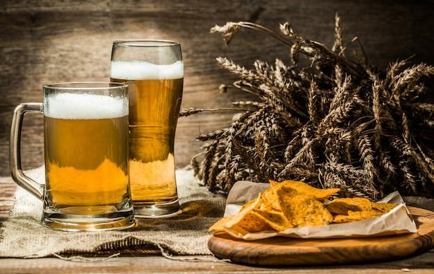 Caneca, copo de cerveja na mesa de madeira com espigas de trigo