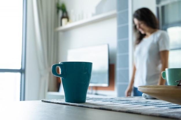 Caneca da manhã de café na mesa no fundo de uma menina.