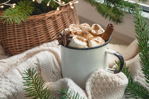 Caneca de aquecimento de inverno de chocolate com marshmallow no peitoril da janela