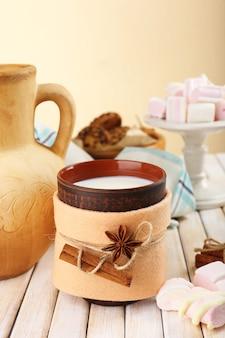 Caneca de bebida quente decorada com feltro na mesa de madeira