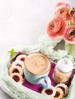 Caneca de biscoitos do café e de flores cor-de-rosa do ranúnculo. pequeno-almoço festivo feriado. mãe dia dos namorados