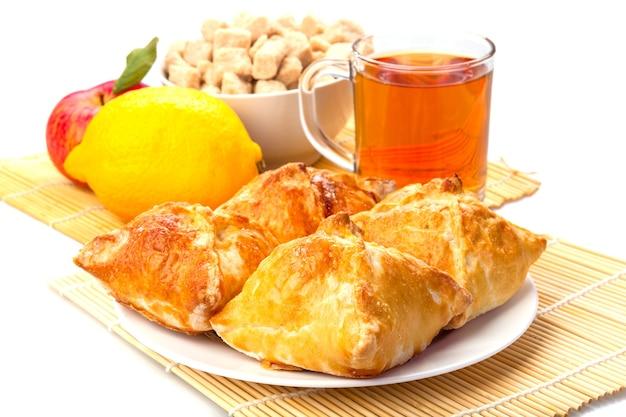 Caneca de bolos de chá em um prato, limão, maçã com folhas verdes e açúcar em uma tigela em uma cama de juncos em branco