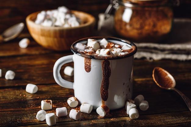 Caneca de cacau com marshmallows. pote de cacau em pó e tigela de marshmallow no pano de fundo.