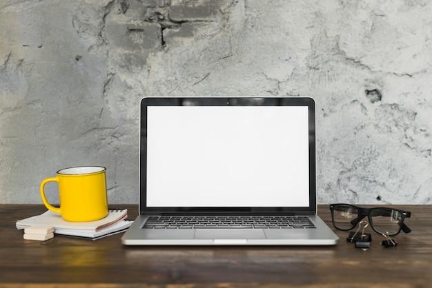 Caneca de café amarela e laptop aberto com material de escritório na mesa de madeira