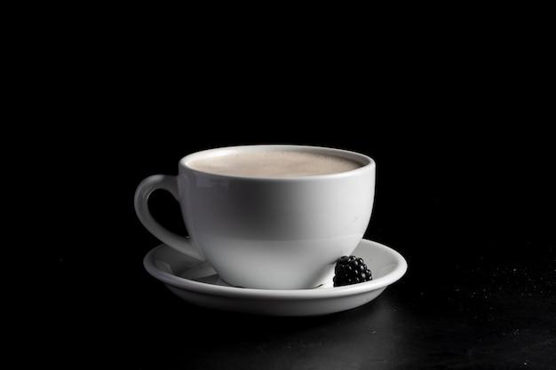 Caneca de café branco com café raf e amoras em um pires