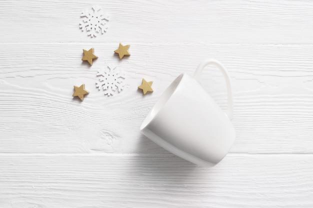 Caneca de café branco com cones de natal e estrelas.