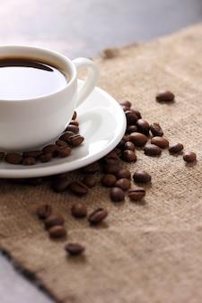 Caneca de café branco em saucer e grãos de café espalhados na vista superior de toalha de mesa de serapilheira.