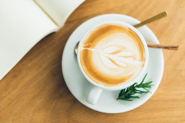 Caneca de café branco. o café é um latte. mesa na mesa de madeira em estilo vintage