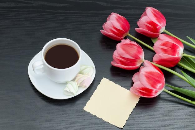 Caneca de café, cartão postal em branco e tulipas cor de rosa