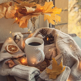 Caneca de café cercada de suéteres e decoração de outono