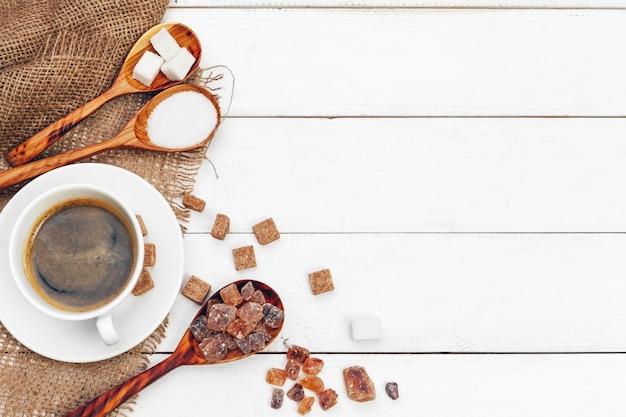 Caneca de café com fatias de açúcar no fundo da mesa de madeira