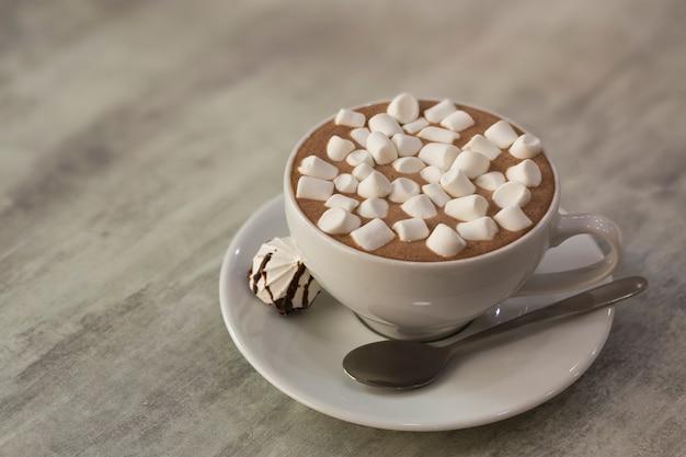 Caneca de café com marshmallows no prato de porcelana na luz de fundo