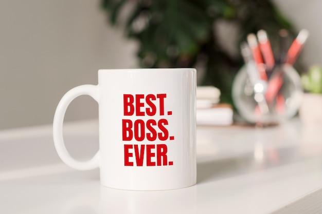 Caneca de café com o texto melhor. chefe. eyer. na superfície do local de trabalho.