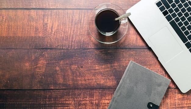 Caneca de café, computador portátil, livro na secretária.