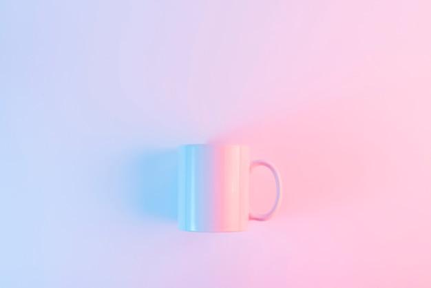 Caneca de café cor-de-rosa contra o fundo cor-de-rosa com copyspace para escrever o texto