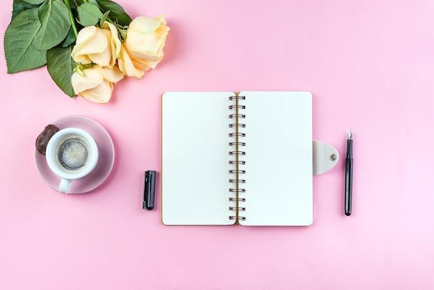 Caneca de café da manhã no café da manhã, caderno vazio, lápis e rosa