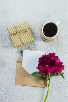 Caneca de café da manhã no café da manhã, caixa de presente ou presente, nota vazia, cartão e flores de peônia rosa