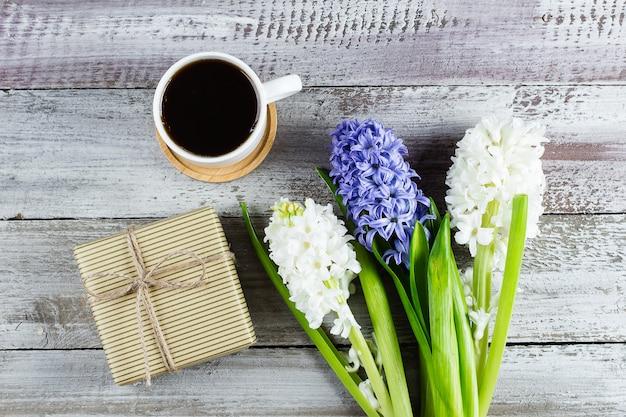 Caneca de café da manhã para o café da manhã, caixa ou presente atual e flores brancas e azuis do jacinto. vista do topo