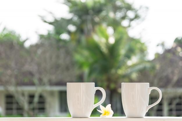 Caneca de café dois branco no jardim.