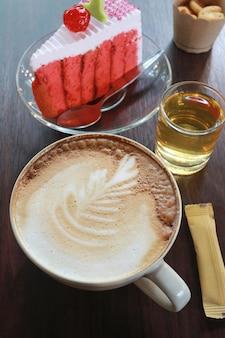 Caneca de café e bolo de cereja em uma mesa de madeira marrom.