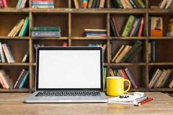 Caneca de café e laptop com artigos de papelaria na mesa de madeira na biblioteca