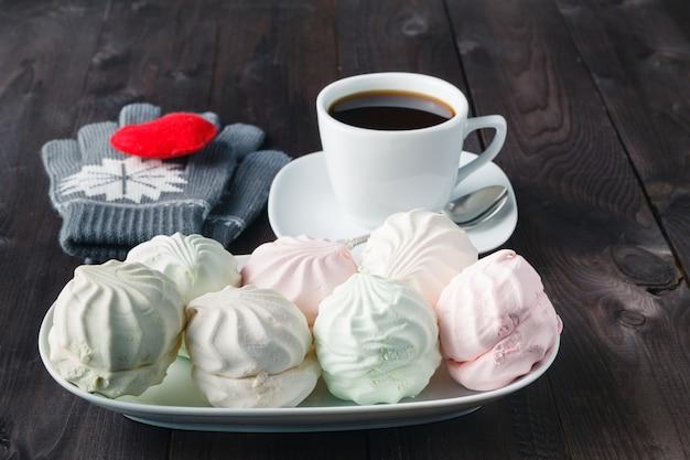 Caneca de café e marshmallow na mesa de madeira