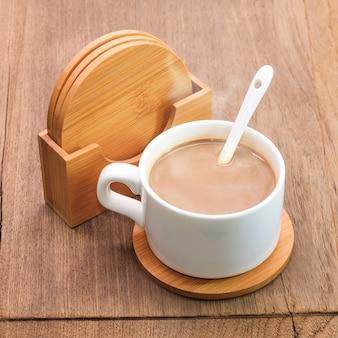 Caneca de café e porta copos da bebida no fundo de madeira.