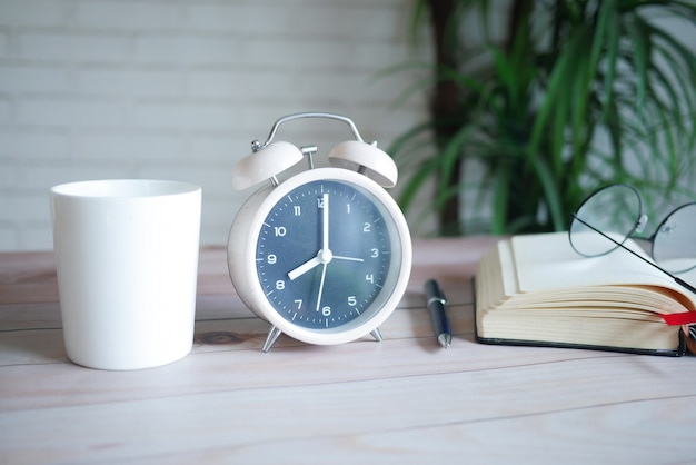 Caneca de café e relógio na mesa fecham