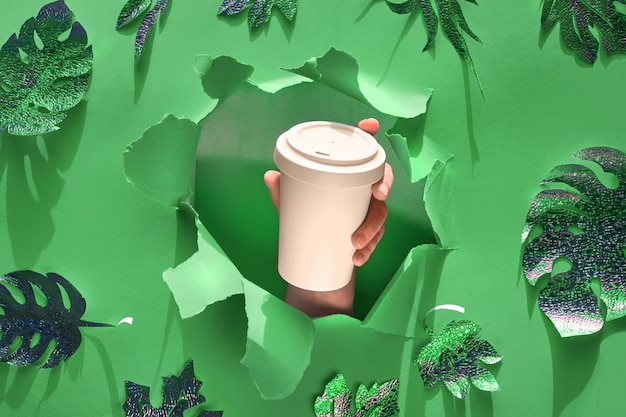 Caneca de café eco reutilizável elegante, copo de bambu com tampa na mão através do orifício do papel. fundo de papel verde com folhas exóticas, maquete de resíduos zero de papel artesanal, cópia-espaço.
