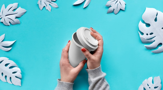 Caneca de café eco reutilizável elegante viagem, copo de bambu com tampa nas mãos.