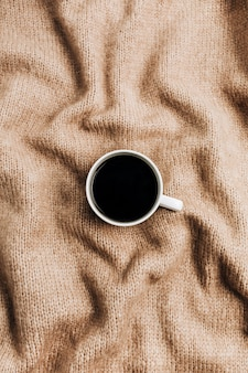 Caneca de café em fundo de lã marrom. camada plana, vista superior