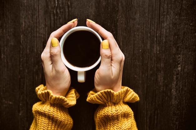 Caneca de café em uma mão feminina.