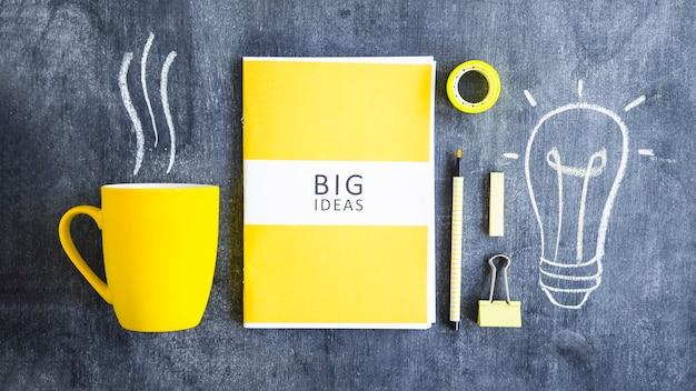 Caneca de café; grandes ideias; artigos de papelaria e lâmpada desenhada na lousa