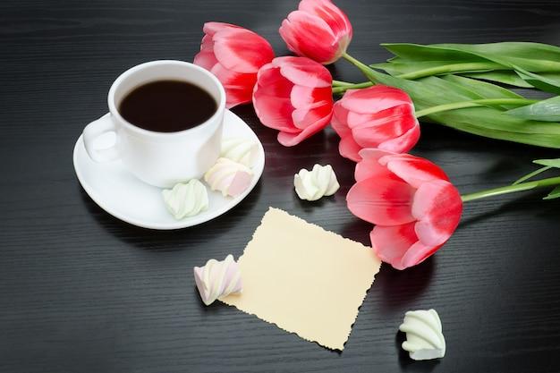 Caneca de café, marshmallows, cartão postal em branco e tulipas cor de rosa. fundo preto.