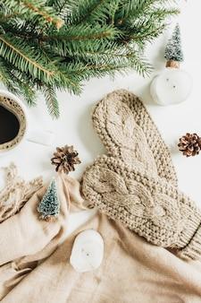 Caneca de café, moldura de grinalda de ramos de abeto, luvas de malha, manta bege e decorações. composição do feriado de natal. camada plana, vista superior