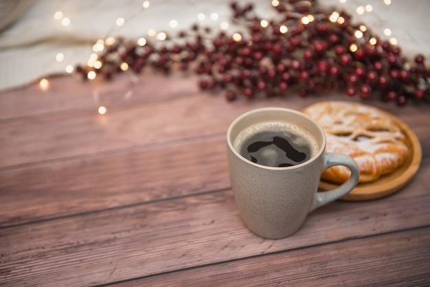 Caneca de café no fundo de madeira, no bolo apetitoso e nas luzes de natal, foco seletivo.
