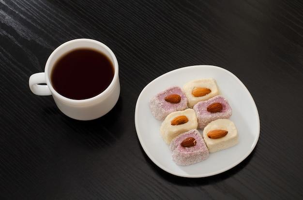 Caneca de café, pires com delícia turca em uma mesa preta, vista de cima