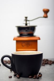 Caneca de café preta com grãos de café caiu ao lado de um fundo de moedor de café.