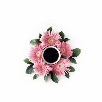 Caneca de café preta e buquê de flores de gerbera rosa em branco