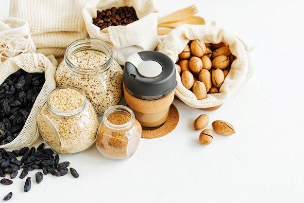 Caneca de café reutilizável, produza saquinhos cheios de nozes e frutas secas. frascos de vidro com sêmolas. compra de alimentos com desperdício zero. vida livre de resíduos