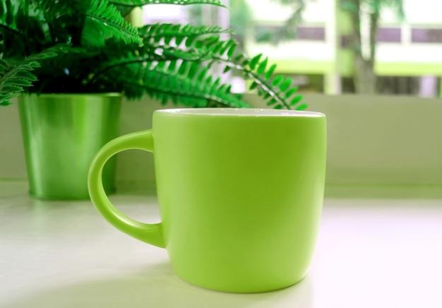 Caneca de café verde na mesa com uma samambaia em vaso